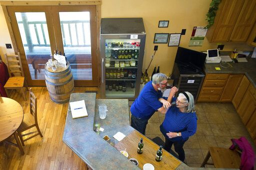 In this Friday, April 26, 2019 photo, Rudi and Mary Hofmann enjoy a toast at Sunset Lake Vineyards & Winery in rural Carlock, Ill. Mary Hofmann, formerly Mary Rouser, was a McLean County farm girl who married Rudi Hofmann, a Bavarian farm boy, and they lived in Germany for years. They returned to McLean County in the 1990s, bought a farm in rural Carlock, planted grapes and opened White Oak Vineyards and Winery in 2003. It was renamed to Sunset Lake Vineyards & Winery a few years ago. (Lewis Marien/The Pantagraph via AP)