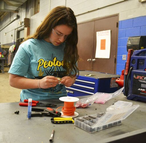 Kankakee Area Career Center student Angelle Vanderwarf crimps and solders wiring connections on Tuesday, April 30, 2019. A senior and cheerleader at Beecher High School, Vanderwarf is a leader in the automotive technology program at the Kankakee Area Career Center.  (Laura McElroy/The Daily Journal via AP)