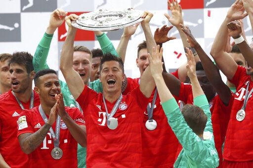Bayern's Robert Lewandowski lifts the trophy to celebrate Bayern's 7th straight Bundesliga title after the German Soccer Bundesliga match between FC Bayern Munich and Eintracht Frankfurt in Munich, Germany, Saturday, May 18, 2019.