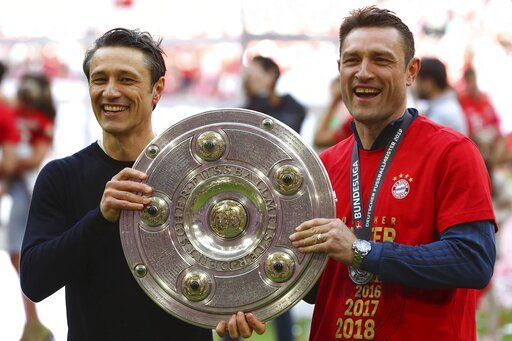 Bayern coach Nikon Kovac, left, and his brother Robert hold the trophy to celebrate Bayern's 7th straight Bundesliga title after the German Soccer Bundesliga match between FC Bayern Munich and Eintracht Frankfurt in Munich, Germany, Saturday, May 18, 2019.