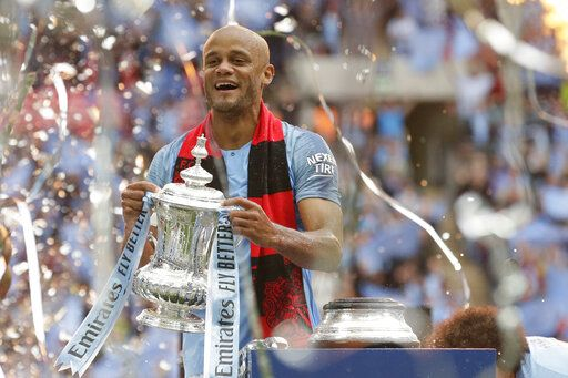 Manchester City's team captain Vincent Kompany lifts the trophy after winning the English FA Cup Final soccer match between Manchester City and Watford at Wembley stadium in London, Saturday, May 18, 2019. Manchester City won 6-0.