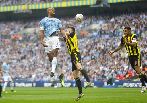 Manchester City's Vincent Kompany, left, jumps for a header with Watford's Craig Cathcart during the English FA Cup Final soccer match between Manchester City and Watford at Wembley stadium in London, Saturday, May 18, 2019.