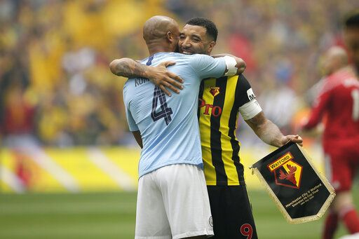 Manchester City's Vincent Kompany, left, hugs Watford's Troy Deeney before the English FA Cup Final soccer match between Manchester City and Watford at Wembley stadium in London, Saturday, May 18, 2019.