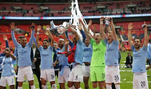 Manchester City's Vincent Kompany lifts the trophy as celebrates with his teammates after winning the English FA Cup Final soccer match between Manchester City and Watford at Wembley stadium in London, Saturday, May 18, 2019. Manchester City won 6-0.