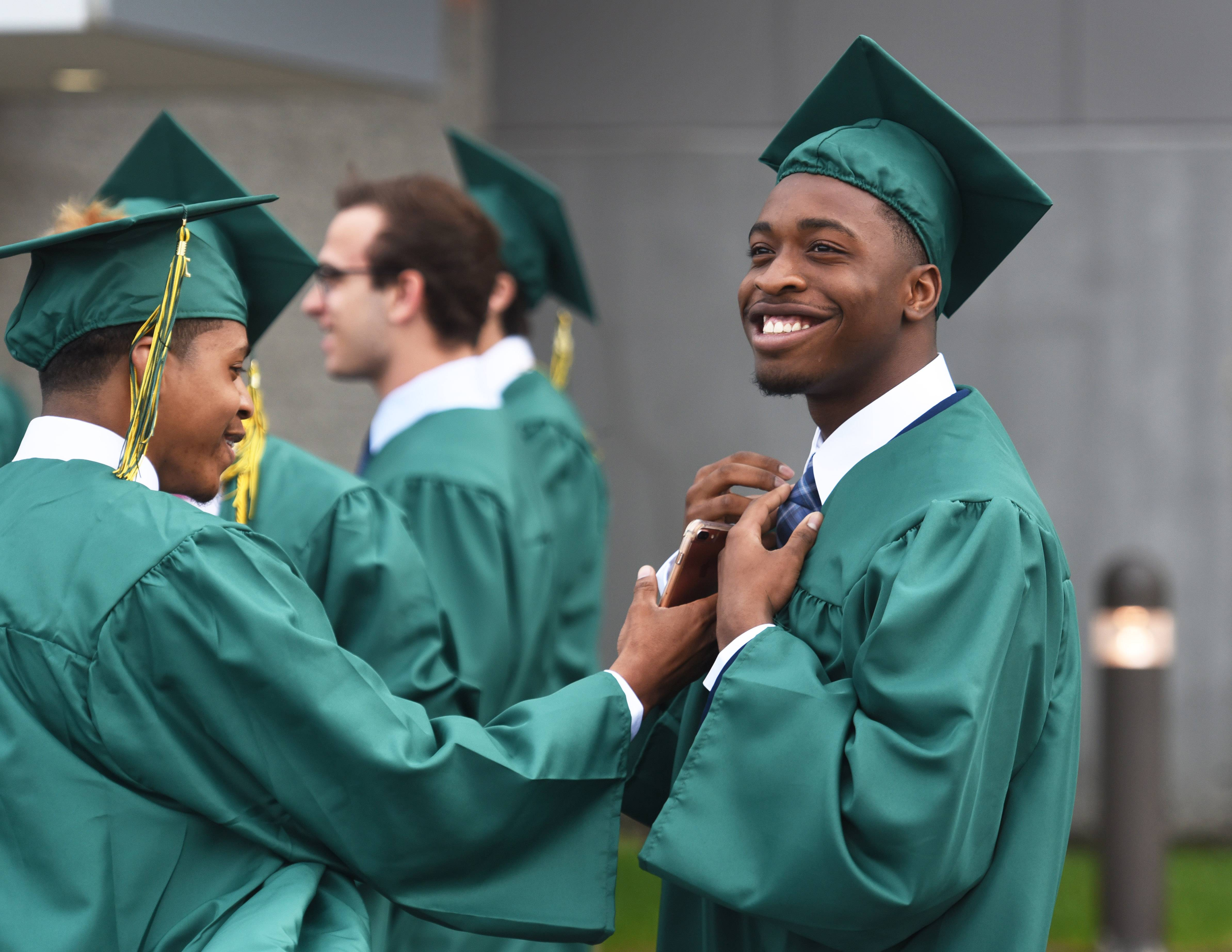 Fremd High School student Anthony Garner, right, is all smiles as schoolmate Brandon Nutall, left, checks out his tie before the start of Monday's graduation ceremony at the Sears Centre in Hoffman Estates.
