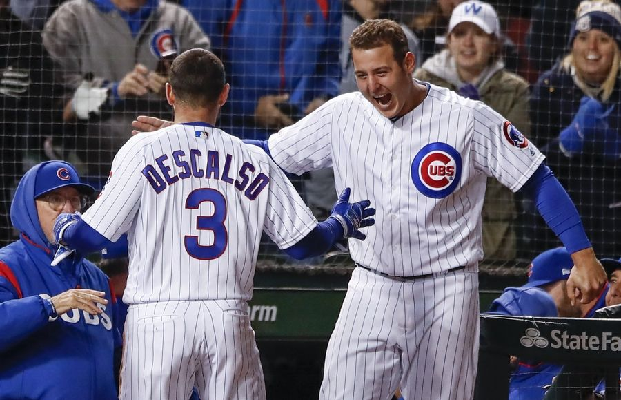 Chicago Cubs' Daniel Descalso, center, celebrates with Anthony Rizzo, right, after hitting three-run triple against the Philadelphia Phillies during the eight inning of a baseball game, Monday, May 20, 2019, in Chicago.