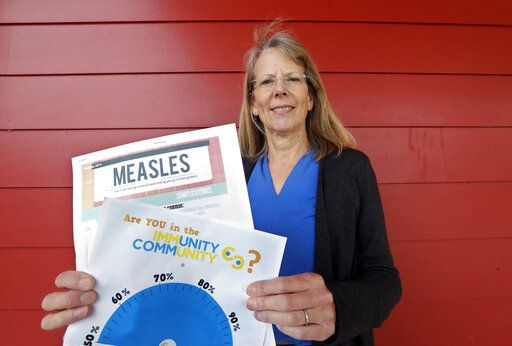 "In this photo taken Wednesday, May 15, 2019, Vashon Island High School nurse Sarah Day holds information about measles vaccinations as she poses for a photo in Vashon Island, Wash. Since Day began communal living on Vashon Island more than 20 years ago, the registered nurse has been advocating for getting kids their shots against a loud contingent of anti-vaccine parents in the close-knit community of about 11,000 that's accessible only by ferry, a serene 20-minute ride from Seattle. And it may now be working, thanks to a ""perfect storm"" of changes being felt on the island, Day said."