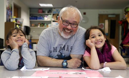 In this photo taken Wednesday, May 15, 2019, Gator Lanphear poses for a photo with his twin 6-year-old daughters Scarlett, left, and Leilani in Vashon Island, Wash. Lanphear said he not only immunizes his twin daughters but instills in them the importance of getting their shots as a heroic act. The number of philosophical exemptions in Vashon has decreased dramatically, but overall, there are still 11.6 percent of students whose families elect not to vaccinate.
