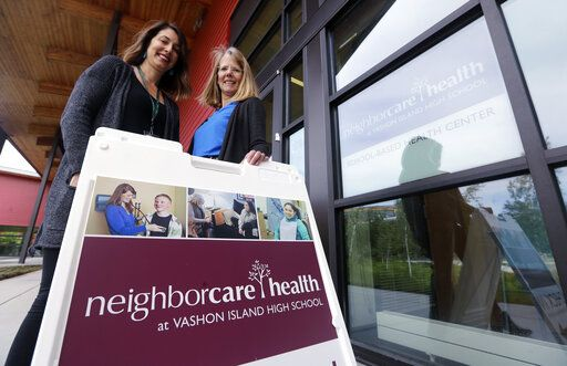 In this photo taken Wednesday, May 15, 2019, Neighborcare Health clinic manager Stephanie Keller, left, stands with Vashon Island High School nurse Sarah Day at the school campus clinic, where top service provided at the student-based health center is vaccinations, in Vashon Island, Wash. The idyllic island near Seattle known for its counterculture lifestyle and low immunization rates is seeing an increase in the number of children vaccinated for measles and other diseases. Keller said the center has received a spike in calls from concerned parents as Washington state struggles to contain a measles outbreak