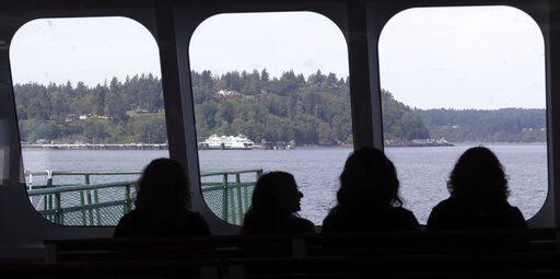 In this photo taken Wednesday, May 15, 2019, passengers sit behind windows at the front of a ferry boat as it approaches Vashon Island, Wash. An idyllic island near Seattle known for its counterculture lifestyle and low immunization rates is seeing an increase in the number of children vaccinated for measles and other diseases. Advocates attribute the rising vaccination numbers on Vashon Island to increasingly visible pro-vaccine information, expanded access to shots and media coverage of measles outbreaks in the Pacific Northwest and New York this year.
