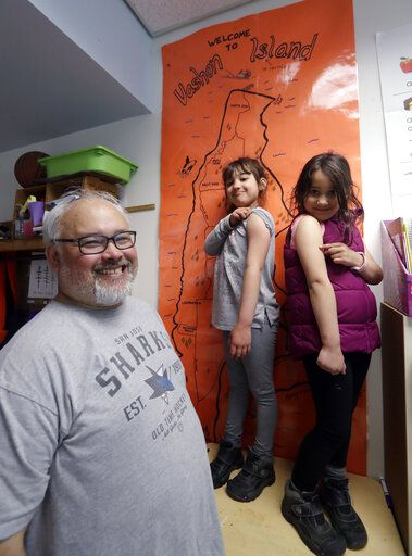 In this photo taken Wednesday, May 15, 2019, Gator Lanphear smiles as his twin six-year-old daughters Scarlett, center, and Leilani show off where on their arms they received their measles immunizations while posing for a photo in Vashon Island, Wash. Lanphear said he not only immunizes his twin daughters but instills in them the importance of getting their shots as a heroic act. The number of philosophical exemptions in Vashon has decreased dramatically, but overall, there are still 11.6 percent of students whose families elect not to vaccinate.