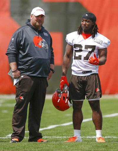 "FILE - In this May 15, 2019, file photo, Cleveland Browns' Kareem Hunt (27) talks with head coach Freddie Kitchens during an NFL football organized team activity session at the team's training facility in Berea, Ohio. Kitchens has been watching Kareem Hunt work toward redemption. On Sunday, May 19, Kitchens showed the running back that he's got his full support. Kitchens and general manager John Dorsey surprised Hunt by attending his baptism at True Vine Missionary Baptist Church on Cleveland's east side. Hunt, who has been suspended eight games by the NFL for two physical altercations, including one in which he shoved and kicked a woman, said last week he wanted ""to feel reborn.�(AP Photo/Ron Schwane, File)"