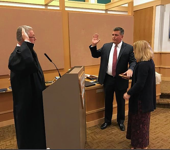 New Buffalo Grove Trustee Gregory Pike, center, is sworn in Monday by Lake County Judge Charles Johnson. Pike's wife, Elysa, is at his left.