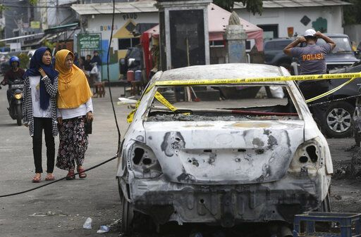 Muslim women walk near a burnt car in Jakarta, Indonesia, Wednesday, May 22, 2019. Supporters of the losing presidential candidate burned vehicles and battled police and the government announced restrictions on social media.