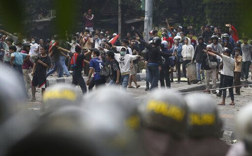 Supporters of the losing presidential candidate clash with police Wednesday, May 22, 2019, in Jakarta, Indonesia. A number of people have died and dozens of vehicles burned as rioters took over neighborhoods in central Jakarta, throwing rocks and Molotov cocktails at police who responded with tear gas, water cannon and rubber bullets..