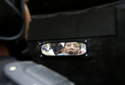 A protester shouts slogans as he is seen through the shield of a riot police officer in Jakarta, Indonesia, Wednesday, May 22, 2019. Supporters of an unsuccessful presidential candidate clashed with security forces in the Indonesian capital on Wednesday, burning vehicles and throwing rocks at police using tear gas and rubber bullets.