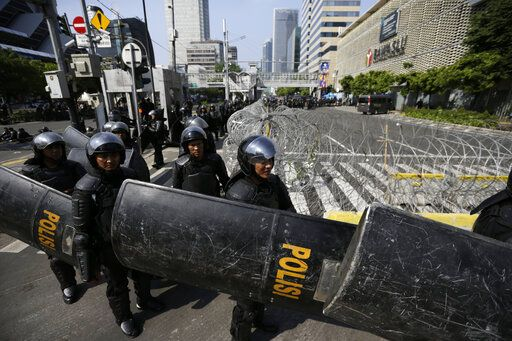 Riot police officers take their position outside the building that house the Election Supervision Board in Jakarta, Indonesia, Wednesday, May 22, 2019. Supporters of an unsuccessful presidential candidate clashed with security forces in the Indonesian capital on Wednesday, burning vehicles and throwing rocks at police using tear gas and rubber bullets.