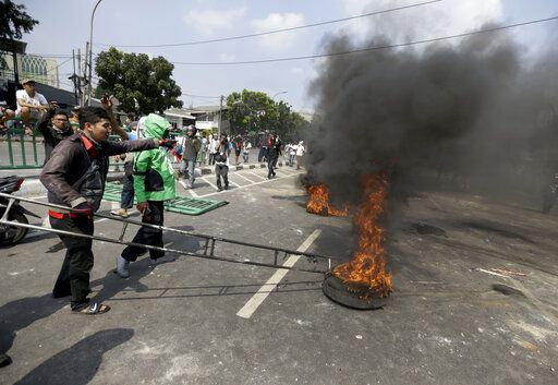 Protesters burn tires on a street during a clash with the police in Jakarta, Indonesia, Wednesday, May 22, 2019. Supporters of an unsuccessful presidential candidate clashed with security forces in the Indonesian capital on Wednesday, burning vehicles and throwing rocks at police using tear gas and rubber bullets.