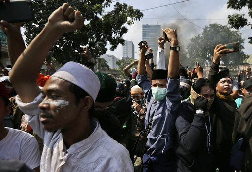 Protesters raise their fists as they taunt officers during a clash with the police in Jakarta, Indonesia, Wednesday, May 22, 2019. Supporters of an unsuccessful presidential candidate clashed with security forces in the Indonesian capital on Wednesday, burning vehicles and throwing rocks at police using tear gas and rubber bullets.