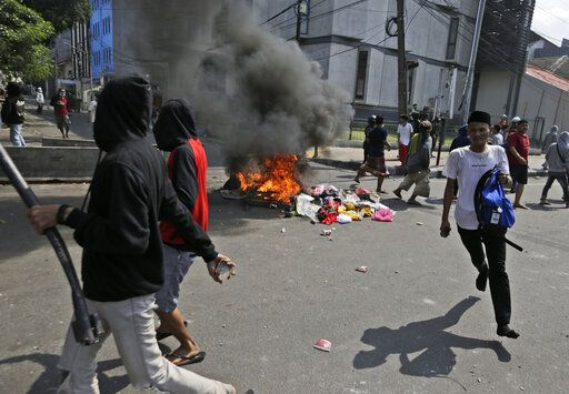 Protesters walk past burning garbage during a clash with the police in Jakarta, Indonesia, Wednesday, May 22, 2019. Supporters of an unsuccessful presidential candidate clashed with security forces in the Indonesian capital on Wednesday, burning vehicles and throwing rocks at police using tear gas and rubber bullets.