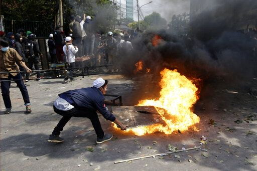 Protesters try to put out fire from a burning tyre in Jakarta, Indonesia, Wednesday, May 22, 2019. Supporters of an unsuccessful presidential candidate clashed with security forces in the Indonesian capital on Wednesday, burning vehicles and throwing rocks at police using tear gas and rubber bullets.