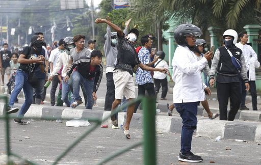Supporters of the losing presidential candidate throw rocks at police Wednesday, May 22, 2019, in Jakarta, Indonesia. A number of people have died and dozens of vehicles burned as rioters took over neighborhoods in central Jakarta, throwing rocks and Molotov cocktails at police who responded with tear gas, water cannon and rubber bullets..