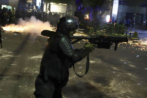 An Indonesian riot police officer fires a tear gas launcher to disperse supporters of Indonesian presidential candidate Prabowo Subianto in Jakarta, Indonesia, early Wednesday, May 22, 2019. Supporters of the unsuccessful presidential candidate clashed with security forces and set fire to a police dormitory and vehicles in the Indonesian capital on Wednesday after the release of official election results.