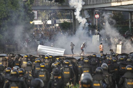 Indonesian riot police officers fire a tear gas launcher to disperse supporters of Indonesian presidential candidate Prabowo Subianto in Jakarta, Indonesia, Wednesday, May 22, 2019. Supporters of the unsuccessful presidential candidate clashed with security forces and set fire to a police dormitory and vehicles in the Indonesian capital on Wednesday after the release of official election results.