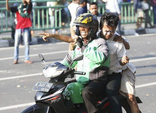 A Grab bike driver rides carries an injured supporter of Indonesian presidential candidate Prabowo Subianto during a clash with Indonesian police in Jakarta, Indonesia, Wednesday, May 22, 2019. Supporters of the unsuccessful presidential candidate clashed with security forces and set fire to a police dormitory and vehicles in the Indonesian capital on Wednesday after the release of official election results.