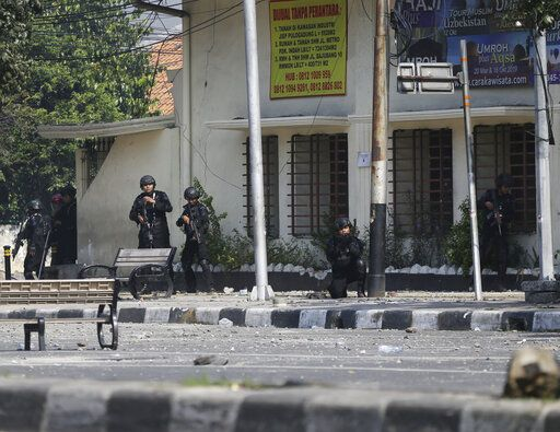 Indonesian police take position during a clash with supporters of Indonesian presidential candidate Prabowo Subianto in Jakarta, Indonesia, Wednesday, May 22, 2019. Supporters of the unsuccessful presidential candidate clashed with security forces and set fire to a police dormitory and vehicles in the Indonesian capital on Wednesday after the release of official election results.