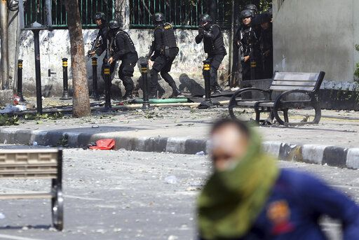 A supporter of Indonesian presidential candidate Prabowo Subianto runs during a clash with the police in Jakarta, Indonesia, Wednesday, May 22, 2019. Supporters of the unsuccessful presidential candidate clashed with security forces and set fire to a police dormitory and vehicles in the Indonesian capital on Wednesday after the release of official election results.