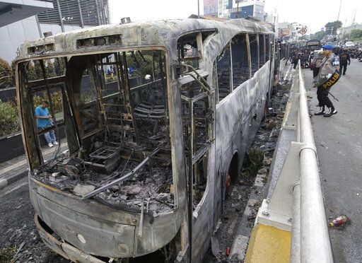 Indonesian police check burnt buses in Jakarta, Indonesia, Wednesday, May 22, 2019. Supporters of the losing presidential candidate burned vehicles and battled police and the government announced restrictions on social media.