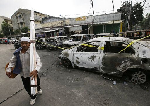 A street vendor walks near burnt cars in Jakarta, Indonesia, Wednesday, May 22, 2019. A number of people have died and dozens of vehicles burned as rioters took over neighborhoods in central Jakarta, throwing rocks and Molotov cocktails at police who responded with tear gas, water cannon and rubber bullets.