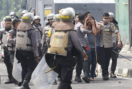 Indonesian police arrest a supporter of the losing presidential candidate in Jakarta, Indonesia, Wednesday, May 22, 2019. Supporters of the losing presidential candidate burned vehicles and battled police and the government announced restrictions on social media.