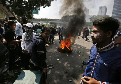Protesters rest near burning tires during a clash with the police in Jakarta, Indonesia, Wednesday, May 22, 2019. Supporters of an unsuccessful presidential candidate clashed with security forces in the Indonesian capital on Wednesday, burning vehicles and throwing rocks at police using tear gas and rubber bullets.