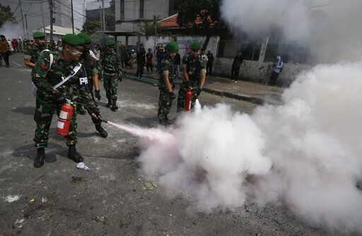 Indonesian soldiers extinguish burning tires during a clash between protesters and the police in Jakarta, Indonesia, Wednesday, May 22, 2019. Supporters of an unsuccessful presidential candidate clashed with security forces in the Indonesian capital on Wednesday, burning vehicles and throwing rocks at police using tear gas and rubber bullets.