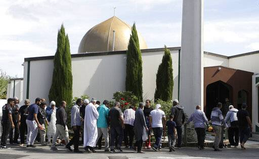 FILE - In this March 23, 2019 file photo, worshippers prepare to enter the Al Noor mosque following the previous week's mass shooting in Christchurch, New Zealand. New Zealand police on Tuesday, May 21, 2019, filed a terrorism charge against the man accused of killing 51 people at two Christchurch mosques. (AP Photo/Mark Baker, File)