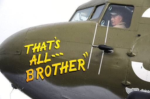 In this April 9, 2019, photo, Pilot Tom Travis sits in the cockpit of the World War II troop carrier That's All, Brother during a stop in Birmingham, Ala. The C-47 aircraft, which led the main Allied invasion of Europe on June 6, 1944, is returning to the continent to participate in events marking the 75th anniversary of D-Day in June. (AP Photo/Jay Reeves)