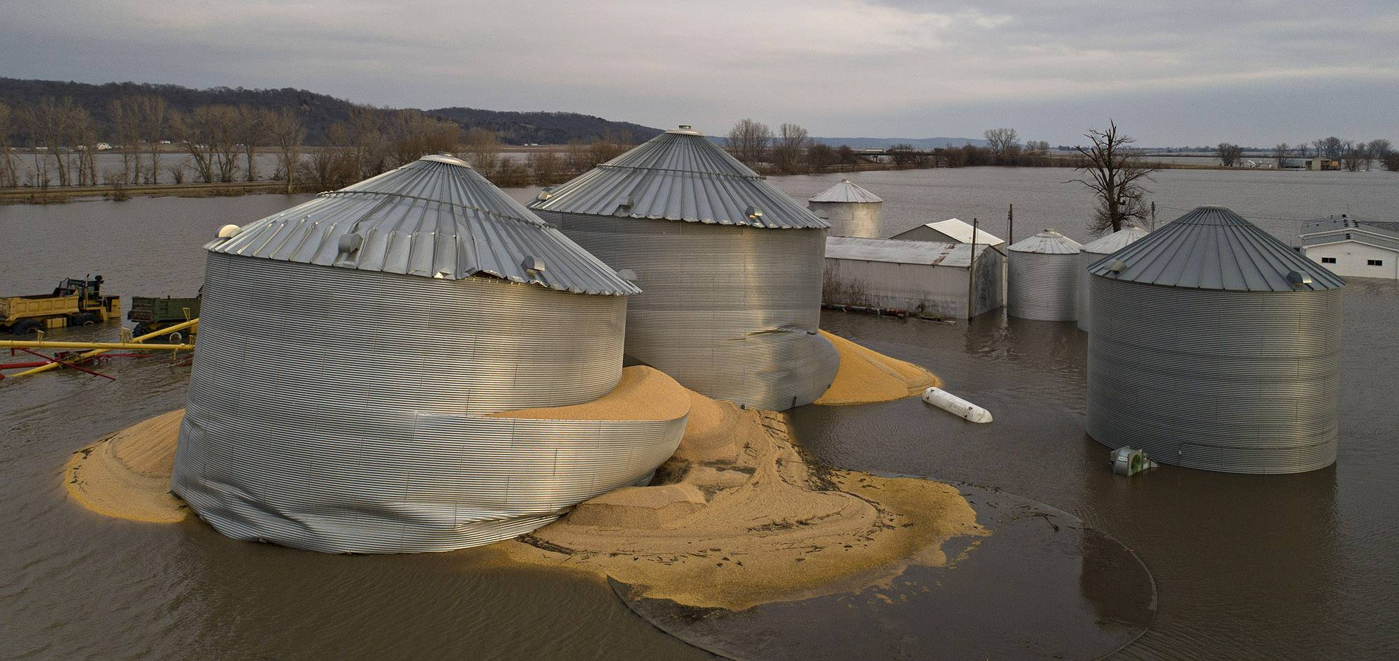 Floodwaters surround corn sitting under a collapsed grain bins in this aerial photograph over Pacific Junction, Iowa.