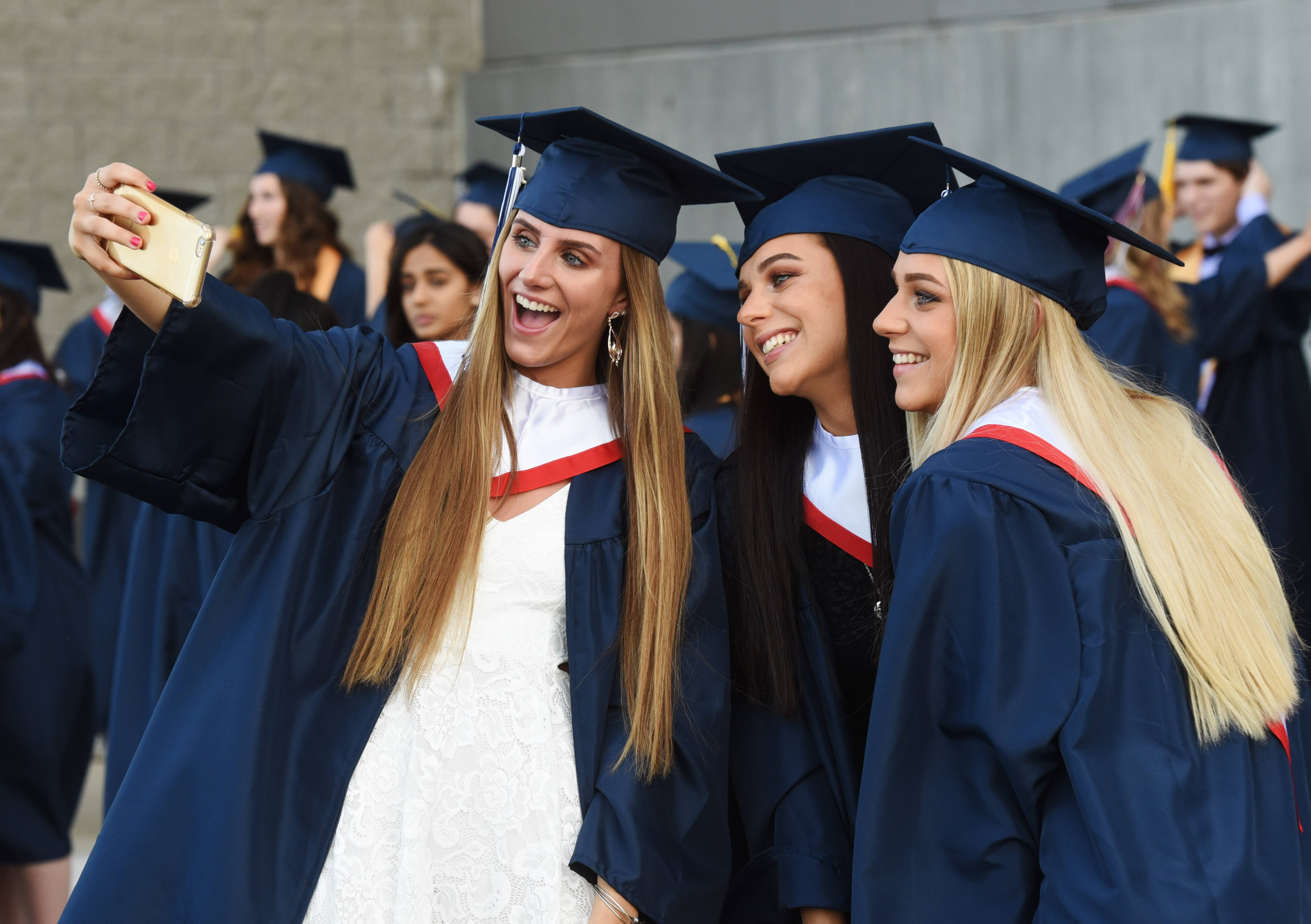 Becca Dahm, left, takes a photo with her cousins, twins Alexa, middle, and Haley Ziemianin prior to the Conant High School graduation at the Sears Centre in Hoffman Estates Wednesday.