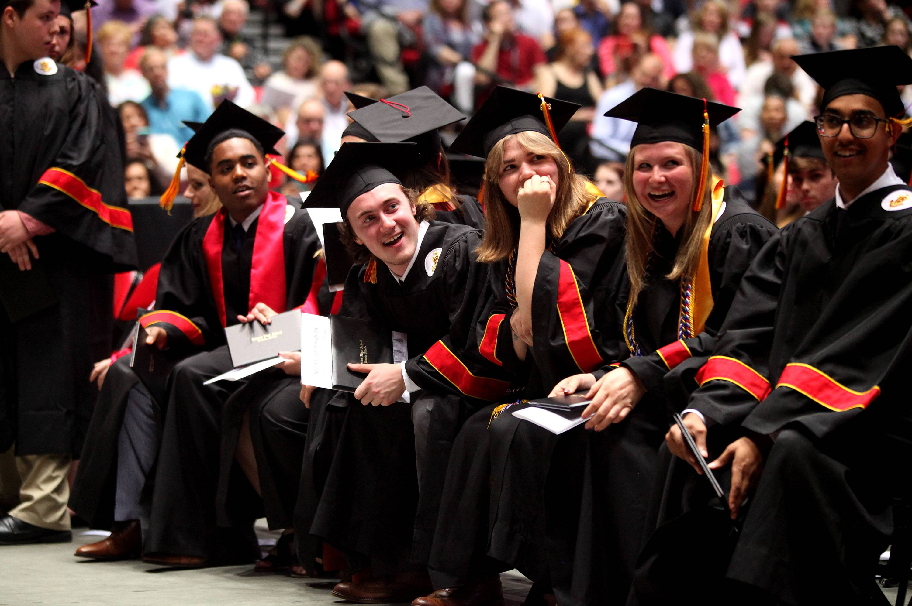 Batavia High School graduates share a laugh during the school's 2019 Commencement Ceremony on May 22 at the Northern Illinois University Convocation Center in DeKalb.
