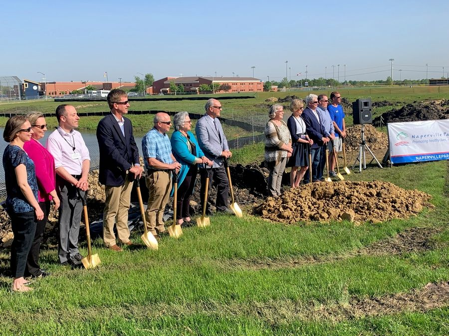 Naperville Park District and city officials donned hard hats and gold-plated shovels to officially begin construction of the 95th Street Community Plaza Wednesday in Naperville.