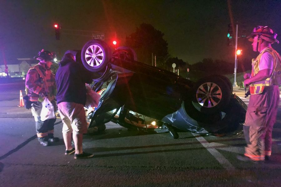 Hoffman Estates firefighters tend to the scene in which Jake Largo of Schaumburg was helped out of his overturned car Saturday night by a group of motorists that included Stefan Knappik of Schaumburg, who was on his way home from senior prom.