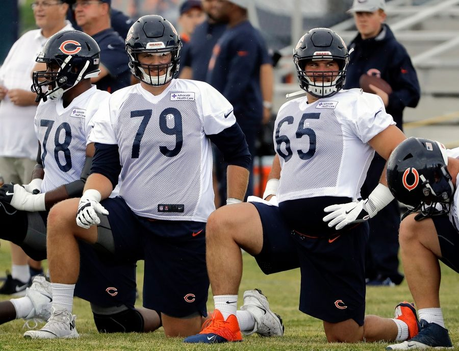 Chicago Bears swing tackle Bradley Sowell (79) and center Cody Whitehair (65) watch teammates during an NFL football training camp in Bourbonnais, Ill., last July. This season, Sowell is moving to tight end and Whitehair is switching to left guard.