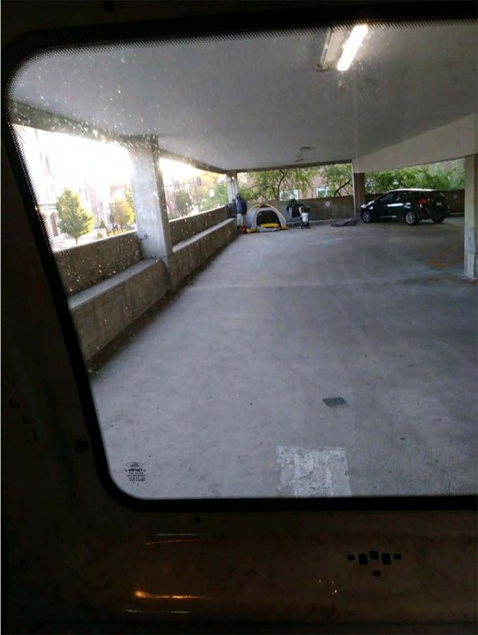 This photo shows a tent pitched in the corner of an Elgin public parking garage.