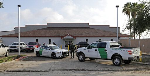 "FILE - In this June 23, 2018 file photo, a U.S. Border Patrol Agent walks between vehicles outside the Central Processing Center in McAllen, Texas. U.S. border agents have temporarily closed their primary facility for processing migrants in South Texas one day after authorities say a 16-year-old died after being diagnosed with the flu at the facility. In a statement released late Tuesday, May 21, 2019, U.S. Customs and Border Protection said it would stop detaining migrants at the processing center in McAllen, Texas. CBP says ""a large number"" of people in custody were found Tuesday to have high fevers."