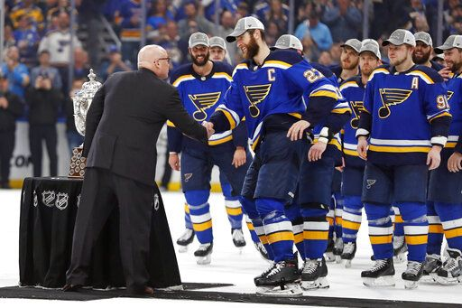 NHL Deputy Commissioner Bill Daly, left, presents the Clarence S. Campbell Bowl to St. Louis Blues' captain Alex Pietrangelo (27) and the rest of the team after the Blues beat the San Jose Sharks after Game 6 of the NHL hockey Stanley Cup Western Conference final series Tuesday, May 21, 2019, in St. Louis. The Blues won 5-1 to win the series 4-2.