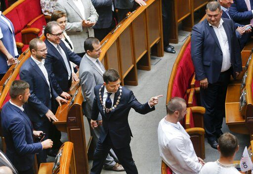 In this photo taken on Monday, May 20, 2019, Ukrainian new President Volodymyr Zelenskiy,  centre, leaves the parliament after his inauguration ceremony in Kiev, Ukraine. Ukrainian TV star Volodymyr Zelenskiy was sworn in as the country's new president on Monday,  and promised to stop the war in the country's east against Russian-backed separatists and immediately disbanded parliament, which he has branded as a group only interested in self-enrichment.
