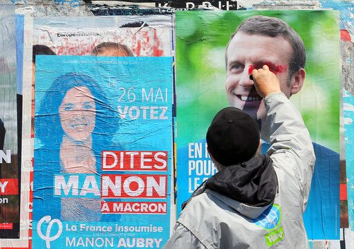 FILE - In this Tuesday, May 21, 2019 file photo, a supporter of French candidate for La France Insoumise party Marion Aubry, scribbles on a campaign poster of French president Emmanuel Macron in Saint-Jean-de-Luz, southwestern France. The European Parliament elections have never been so hotly anticipated or contested, with many predicting that this year's ballot will mark a coming-of-age moment for the euroskeptic far-right movement. The elections start Thursday May 23, 2019 and run through Sunday May 26 and are taking place in all of the European Union's 28 nations.