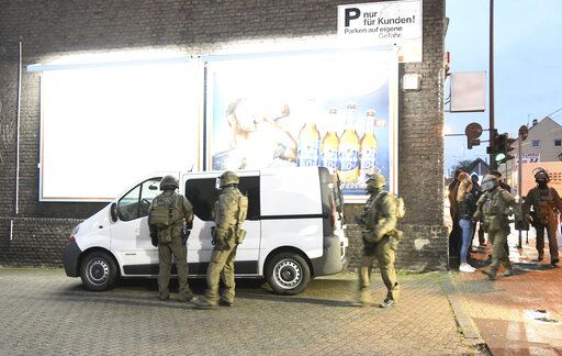 Police officers secure a building in Essen, Germany, Wednesday, May 22, 2019. Police in western Germany are raiding premises linked to an Iraqi gang suspected of involvement in human trafficking, drug dealing, illegal arms trade and forging identity papers.  (Stephan Witte/dpa via AP)
